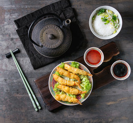 Fried tempura shrimps on lettuce salad with sauces. Served in traditional china plate with chopsticks on wood serving board. Teapot, bowl of rice. Over old metal background. Top view. Asian dinner