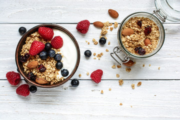 homemade yogurt with oat granola, nuts and fresh berries in a bowl