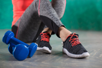 girls legs on sport shoes and dumbbells on wooden background
