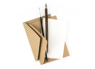 Конверты, бумага, перо и кисточка лежат на столе