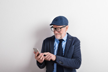 Smart senior man in suit, eyeglasses and cap, holding smartphone
