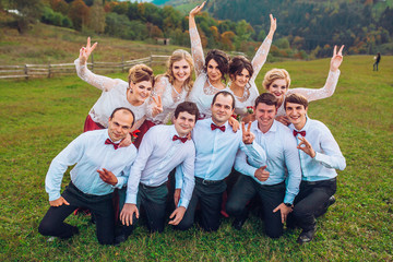 Groomsman and bridesmaids having fun and posing on camera behind beautiful mountains.
