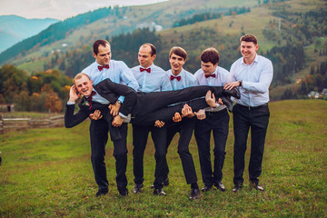young groom and his funny friends groomsman posing for camera and having fun outdoor near mountains. Group of young men with bow tie. Cheerful friends. friends outdoors. Wedding day.