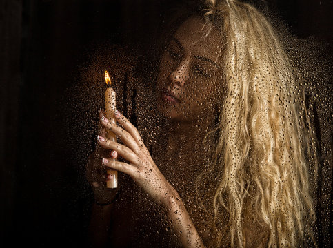 curly nude blonde woman with candle on dark background
