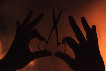 hand holding scissors against a background of fire