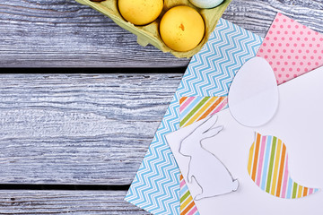 Easter eggs and patterned paper. Colorful paper on gray wood. Make Easter decorations at home.