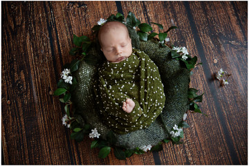 A cute small baby is covered with a green blanket during his first professional photoshoot. He is sleeping.