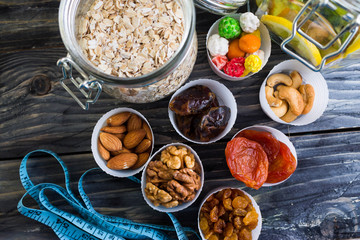 Nuts and dried fruit to the diet on a wooden table in rustic style