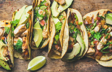 Tacos with grilled chicken, avocado, fresh salsa sauce and limes over rustic wooden background, top view. Healthy low carb and low fat lunch or food for company. Dieting and weight loss concept