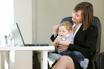 Lovely young working mother and her baby, in her Home Office, Little Break for Cuddling