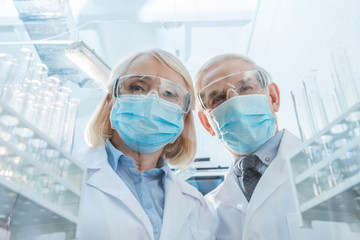 Scientists in protective masks and glasses standing between empty test tubes