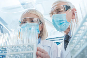 Scientists in protective masks and glasses working with empty test tubes