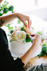 Decorating iced cake with flowers