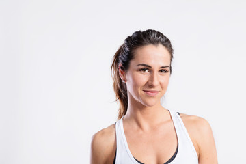 Attractive young fitness woman in white tank top. Studio shot.