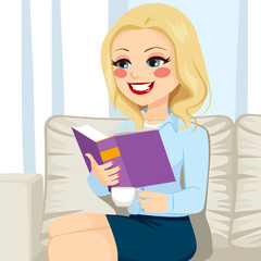Beautiful blonde senior woman reading book relaxing on sofa drinking coffee