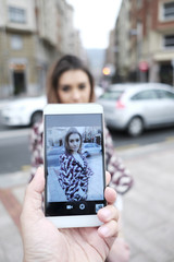 Man makes photos of beautiful woman with his smart phone.