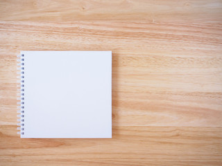white cover notebook on brown wood desk background