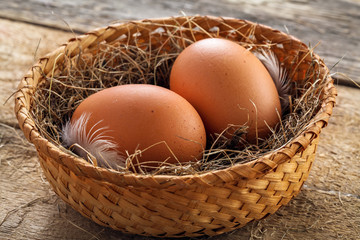 Couple of fresh chicken eggs in a rural basket with hey and feather on a wooden background. Close-up shot.