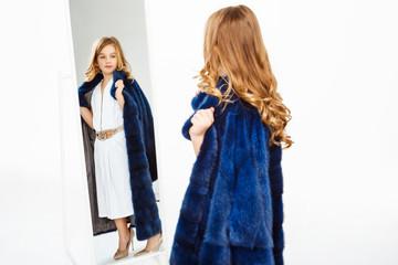 Girl with curls posing in fake fur coat admiring image.