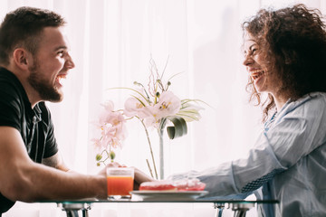 Laughing man and woman sit before bright window