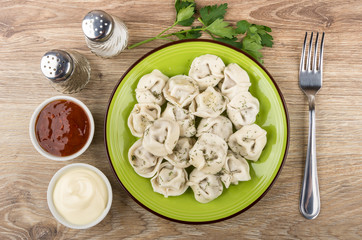 Boiled dumplings, ketchup, mayonnaise, spices and fork on wooden table