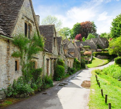 A beautiful sunny morning in  Bibury,  Gloucestershir,  England, UK.  Old street with traditional cottages.