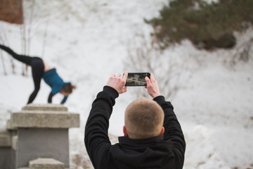 Teenager boy makes photo on smartphone of acrobatic jump girl in winter city park - parkour concept