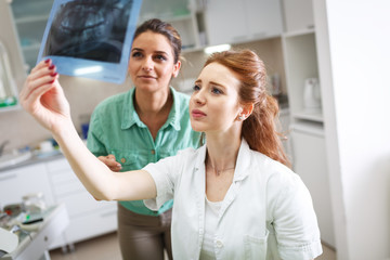 Two female dentist in dental office examining x-ray image.