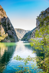 View of beautiful tourist attraction, lake at Matka Canyon in the Skopje surroundings, Macedonia. Branch with leafs in the foreground, vertical composition.