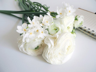 Spring styled stock photo. Still life with daffodils and Persian buttercup flowers, Narcissus, Ranunculus and notebook. Blurred background. Image for blog or social media.