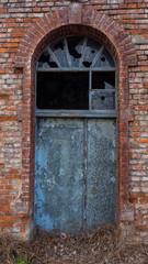 Picture of old, destroyed door with broken window.