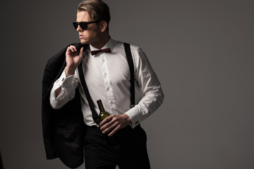 Sharp dressed man in black suit with bottle of wine
