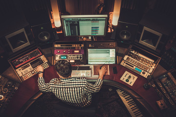 Sound engineer working in boutique recording studio.