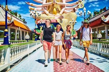 group of tourists exploring buddhist temple in thailand