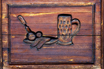Decorative wooden carving on a door.Relief with shape of a pint of beer and sausages on an old gate.