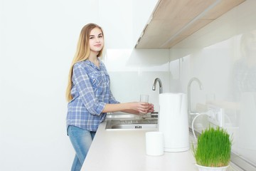 Young beautiful girl in a blue checkered shirt and jeans in the kitchen pouring the glass of water. Morning. home interior.