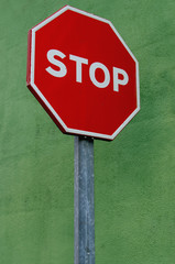 Stop signal over a green painted wall