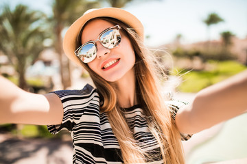 Smile woman in hat and sunglasses taking selfie with mobile phone from hands on summer resort palms background. Summer vocation