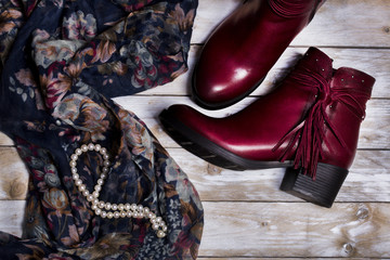 Leather woman boots and scarf on wooden background