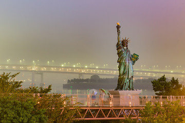 Night view of Statue of Liberty in Tokyo,Statue of Liberty with Rainbow Bridge, Tokyo Tower and Tokyo City in Background at Night,selective focus vintage color