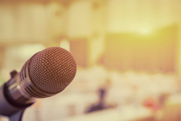 Microphone in concert hall or conference room with defocused bokeh lights in background. Extremely shallow dof. : Vintage style and filtered process..
