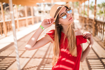 Young white girl standing on the pier in a red sun dress and hat.