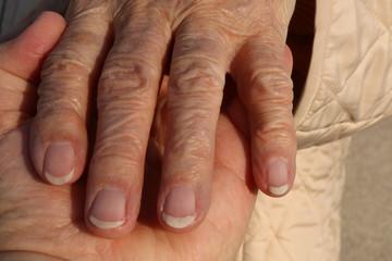 Hands, 50 years old woman holds the Hand of a 90 years old woman (upper Hand), 50 jährige hält die Hand einer 90 jährigen, Symbolfoto für Pflege, Senioren