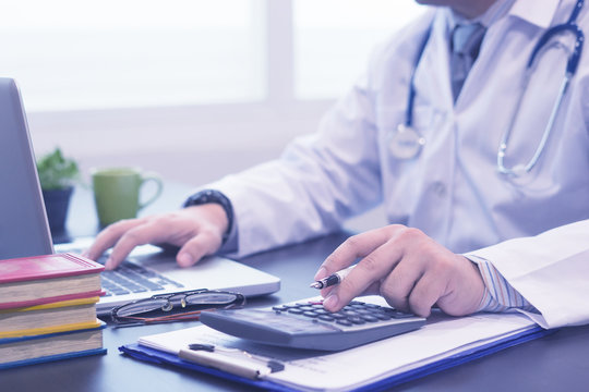 young medical doctor caucasian healthcare professional wearing a white coat with stethoscope in hospital ,doctor's office calculates on an electronic calculator,selective focus,blue color