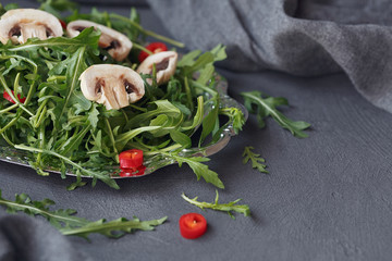 Fresh green arugula with mushrooms and chili pepper on a silver plate on dark gray background.