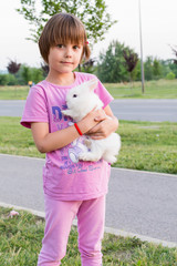 Little girl hugs a rabbit