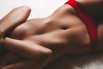 Young pretty woman with perfect tanned body lying down