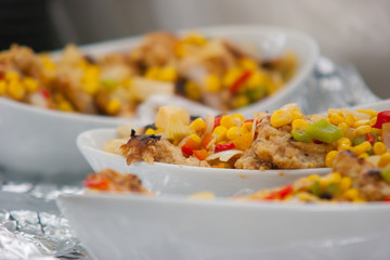 Fish filet served with sweet corn, bell peppers, and chopped tomato
