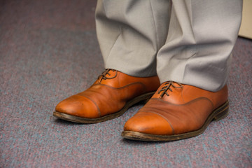 Bright brown men's shoes with gray pants. Groom outlook