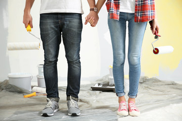 Young couple with paint rollers holding hands together at renewing apartment